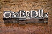 overdue word in mixed vintage metal type printing blocks over grunge wood