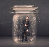 Business man captured in glass jar with hand drawn media icons concept on background
