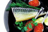 image of smoked mackerel on black plate with caviar