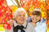 Laughing Grandmother And Granddaughter In The Park With Beautiful Red Leaves