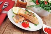 savory sea fish : baked salmon strips with green vegetable salad and tomatoes , red caviar in white bowl , grinder and cutlery , on wooden table