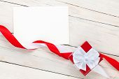 Photo frame card and gift box with ribbon over wooden table background