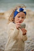 picture of headband  - cute child girl in blue headband plays with stones on the beach - JPG