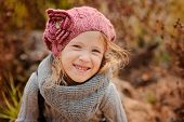 close up autumn portrait of adorable smiling child girl in pink knitted hat