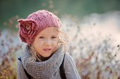 close up portrait of adorable child girl in pink knitted hat and grey sweater