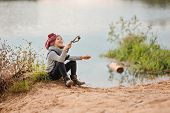 adorable child girl in pink knitted hat having fun on river side