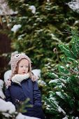 adorable happy child girl in owl knitted hat on the walk in winter snowy garden