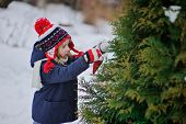 adorable child girl in christmas hat decorating tree in winter snowy garden