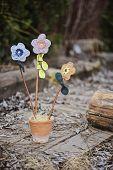 handmade fabric flowers in ceramic pot in spring garden