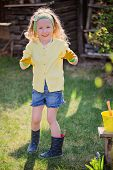 adorable happy child girl plays little gardener and shows rubber gloves in spring garden