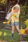 cute child girl with watering can plays little gardener in spring blooming garden