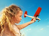 Child playing with plane. Happy girl play outdoors