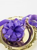 opening ceremony concept- purple ribbon bow on the golden plate