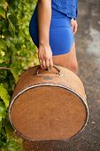 image of mini-skirt  - Detail of antique hat case being held by girl wearing blue mini skirt - JPG