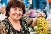 Ukrainian woman aged seller at local grocery market