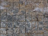 stock photo of sand gravel  - street dirty granite square small gray tiles with rough rough seams and scattered gravel sand and ice - JPG