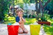 picture of kiddie  - Little blond child boy having fun with splashing water in summer garden - JPG