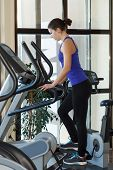 picture of elliptical  - Woman doing exercises with elliptical trainer in gim - JPG
