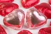 image of two hearts  - Two chocolate hearts in pink wrapping foil close together and surrounded by many other chocolate hearts in red wrapping foil - JPG