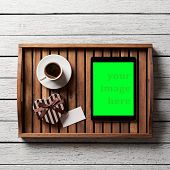 Gift box with blank tag, cup of coffee and digital tablet pc on salver on white wood table.