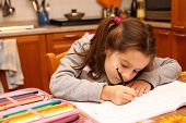 Young Girl Writes With Pencil On The School Book