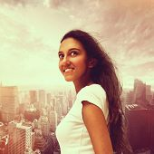 Attractive smiling young Asian woman against a modern cityscape standing sideways looking up into the sky with a happy expression in a conceptual image, square format