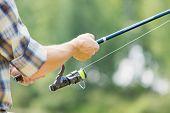 Close up of guy sitting on bridge and fishing