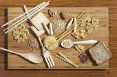 Art Composition Of Pasta, Grains,  Whole Grain Bread, Wooden Kitchen Set Placed On Wooden Background
