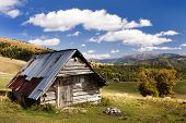 stock photo of chalet  - woody chalet on the mountains with sky and clouds - JPG