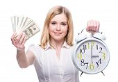 stock photo of holding money  - Portrait of young business woman is holding in hands clock and money isolated on white background discipline and punctual concept.