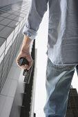 Man holding gun against an skyscraper background