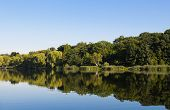 picture of peaceful  - A peaceful lake with trees and reflections during the day with copy space - JPG