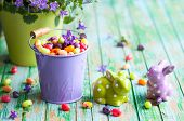 stock photo of jelly beans  - Easter rabbits and buckets with jelly beans on the vintage wooden table - JPG