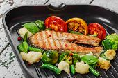 grilled salmon with vegetables on a grill pan