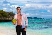 Happy Handsome Young Male Wearing In White Shirt Is Standing On The Tropical Beach