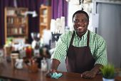 Happy African-american guy waiting for clients in cafe