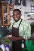 Happy African-american man in uniform looking at camera while pouring drink