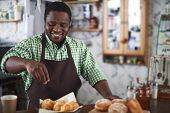Happy young man powdering buns with vanilla sugar in bakery shop