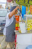PISCO, PERU, MAY 21, 2014:  Local man prepares fresh orange juice on street stand