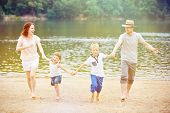 Happy family with children having summer vacation at lake with beach