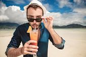 Close up picture of a young casual man on the beach drinking a orange cocktail with a straw while taking off his sunglasses.