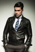 Attractive business man in leather jacket, looking away from the camera with his hands in pockets.