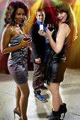 stock photo of seducing  - women seducing a man at a bar or nightclub - JPG