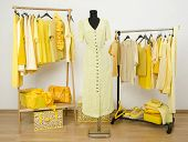 Dressing Closet With Yellow Clothes Arranged On Hangers And A Dress On A Mannequin.