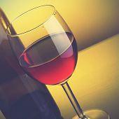 Glass of red wine and bottle. Retro style filtred image