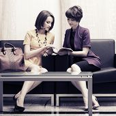 Two young fashion women sitting on a couch in showroom