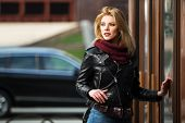 image of jacket  - Young fashion blond woman in leather jacket at the mall door - JPG