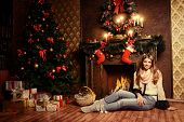 Beautiful smiling girl warms by the fireplace in the cozy Christmas room.