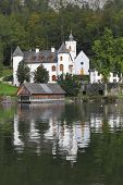 Abbey on the shore of Lake Hallstatt. White buildings are reflected in the smooth water of the lake