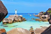 Thailand. Gorgeous beach on the Similan Islands. Middle-aged woman dressed in white doing yoga.  Asana